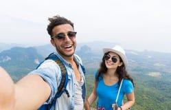 Os pares com trouxas tomam a foto de Selfie sobre Trekking da paisagem da montanha, homem novo e mulher em turistas da caminhada fotos de stock royalty free