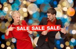 Os pares com venda vermelha assinam sobre luzes de Natal Fotos de Stock
