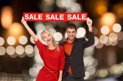 Os pares com venda vermelha assinam sobre luzes de Natal imagem de stock royalty free