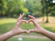 Os pares da moça que fazem o coração dão forma com conceito das mãos, do amor e dos relacionamentos Fotografia de Stock Royalty Free