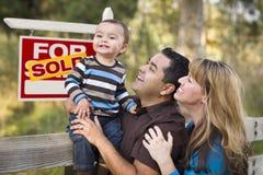 Os pares da raça misturada, bebê, venderam o sinal dos bens imobiliários foto de stock
