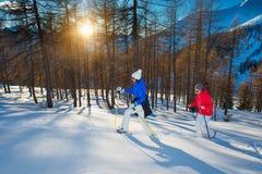 Os pares de amigas andam com os sapatos de neve no por do sol Imagem de Stock