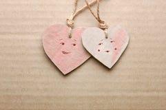Os pares de corações feitos a mão do cartão com caráteres masculinos e fêmeas tirados contra cartão listrado cobrem Fotos de Stock