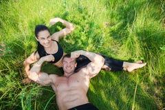 Os pares de desportistas novos encontram-se na grama verde após o exercício fora Foto de Stock Royalty Free