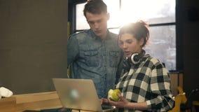 Os pares de dois povos à moda, um indivíduo e uma menina, nos equipamentos modernos urbanos que surfam a Web em bem iluminado esp filme