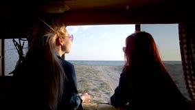 Os pares de jovens mulheres olham ao Sandy Beach e ao mar através da auto janela do reboque no cabelo Boho dos sopros do vento do filme