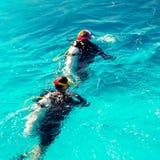 Os pares de mergulhadores nadam no oceano azul fotografia de stock royalty free