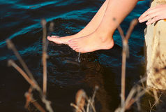 Os pares de pés desencapados tocam na obscuridade - água azul Imagem de Stock Royalty Free