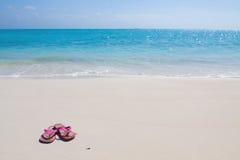 Os pares de sandálias coloridas em uma areia branca encalham Imagem de Stock Royalty Free