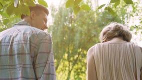 Os pares de sorriso que andam na floresta do verão que guarda a cesta do piquenique suportam a vista, data video estoque