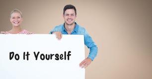 Os pares de sorriso que guardam a placa de conta com fazem-na você mesmo texto neles Foto de Stock Royalty Free