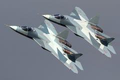 Os pares de Sukhoi T-50 PAK-FA 052 AZUL e de 051 lutadores de jato modernos AZUIS do russo que executam a demonstração migram em  Fotos de Stock