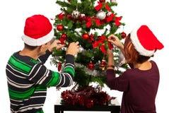 Os pares decoram a árvore de Natal Fotos de Stock Royalty Free