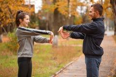 Os pares desportivos felizes contrataram no parque do outono que faz exercícios para as mãos que estão oposto a se imagem de stock royalty free