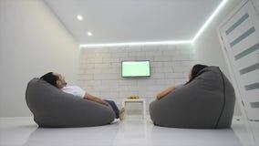 Os pares dirigem a televisão de observação no saco da cadeira O par olha a televisão com tela verde vídeos de arquivo