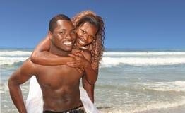 Os pares do americano africano que sorriem na praia Outdo imagens de stock