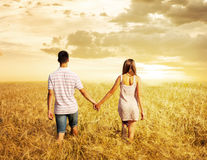 Os pares do amor que andam no por do sol colocam guardar as mãos Fotos de Stock Royalty Free