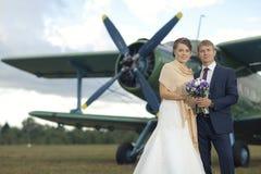 Os pares do casamento aproximam aviões do vintage Foto de Stock