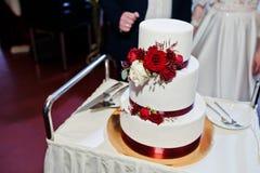 Os pares do casamento cortaram o bolo de casamento com rosas vermelhas e fita Imagem de Stock