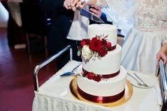 Os pares do casamento cortaram o bolo de casamento com rosas vermelhas e fita Imagens de Stock