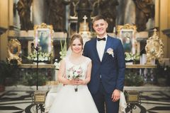 Os pares do casamento permanecem e o noivo casa-se em uma igreja Fotos de Stock
