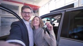 Os pares do consumidor com chaves tomam a foto do selfi no telefone celular perto do veículo comprado novo no concessionário auto vídeos de arquivo