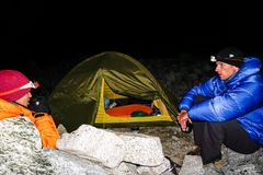 Os pares do montanhista de montanha sentam-se fora de uma barraca na obscuridade e para beber o chá altamente acima no BLANCA de  fotos de stock