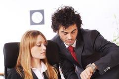Os pares do trabalhador olham o relógio Imagens de Stock Royalty Free