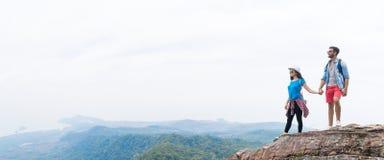 Os pares do turista com a trouxa que guarda as mãos na parte superior da montanha apreciam o panorama bonito da paisagem fotos de stock
