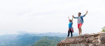 Os pares do turista com a trouxa que mantém as mãos levantadas na parte superior da montanha apreciam o panorama bonito da paisag fotografia de stock royalty free