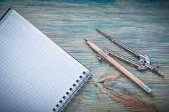 Os pares do vintage de compassos escrevem o caderno verificado no varrão de madeira Imagem de Stock Royalty Free