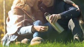 Os pares envolveram no sentimento quente bebendo geral do ar livre do chá confortável junto vídeos de arquivo