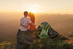 Os pares felizes apreciam a vista bonita nas montanhas Imagem de Stock