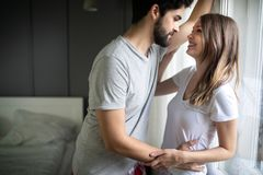 Os pares felizes bonitos de amantes novos est?o abra?ando dentro em casa, com amor e ternura fotografia de stock