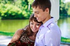Os pares felizes com um ramalhete de rosas vermelhas em um verão estacionam Imagem de Stock Royalty Free