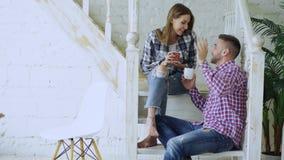 Os pares felizes e loving novos bebem o chá e a fala ao sentar-se em escadas na sala de visitas em casa video estoque