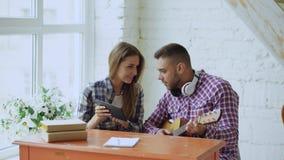 Os pares felizes e loving novos estudam para jogar a guitarra acústica usando o tablet pc e tendo o divertimento ao sentar-se no foto de stock