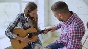 Os pares felizes e loving novos estudam para jogar a guitarra acústica usando o tablet pc e tendo o divertimento ao sentar-se no imagem de stock
