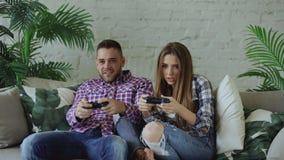 Os pares felizes e loving novos jogam o jogo do console com gamepad e têm o divertimento que senta-se no sofá na sala de visitas  foto de stock