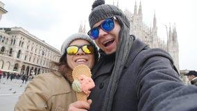 Os pares felizes em Milão que come o gelado que toma a foto do autorretrato do selfie em férias viajam em Itália Férias do invern filme