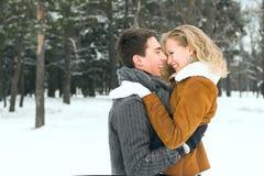 Os pares felizes exteriores no amor que levanta no inverno frio resistem Fotografia de Stock