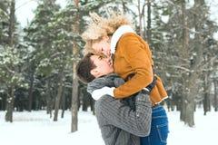 Os pares felizes exteriores no amor que levanta no inverno frio resistem Foto de Stock Royalty Free