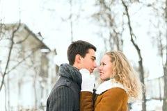 Os pares felizes exteriores no amor que levanta no inverno frio resistem Fotos de Stock