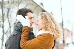 Os pares felizes exteriores no amor que levanta no inverno frio resistem Imagem de Stock