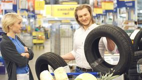 Os pares felizes fazem a escolha com os pneus de carro no shopping vídeos de arquivo