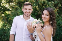 Os pares felizes mostram suas mãos com alianças de casamento Limo do noivo e da noiva foto de stock