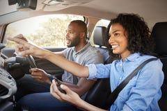 Os pares felizes no carro em uma viagem por estrada navegam com smartphone foto de stock