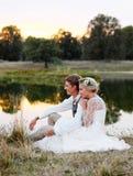 Os pares felizes no casamento attire contra o contexto do lago no por do sol, noivos foto de stock
