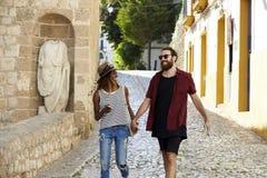 Os pares felizes no feriado guardam as mãos que andam em Ibiza, Espanha Imagens de Stock