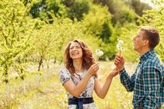 Os pares felizes novos atrativos em uma mola jardinam Imagens de Stock